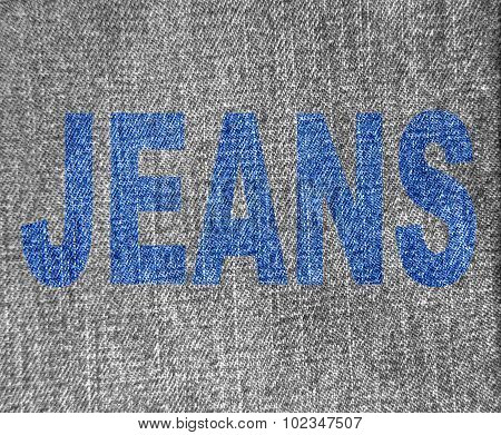 Blue Inscription Jeans Over Grey Jeans Texture Background