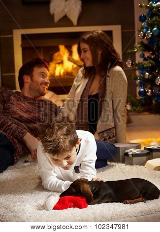 Little boy caressing dachshund puppy receiving for christmas, parents at background.