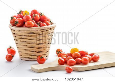 Bunch Of Cherry Tomatoes In A Rattan Basket And On A Wooden Cutting Board