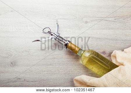 Wine bottle with corkscrew on wooden background.