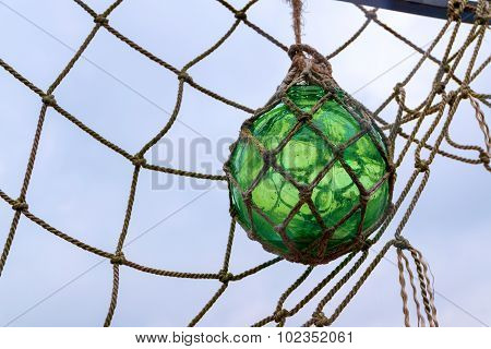 Glass Fishing Float Ball With Rope Knots Hanging In A Fishing Net To Dry Against The Sky