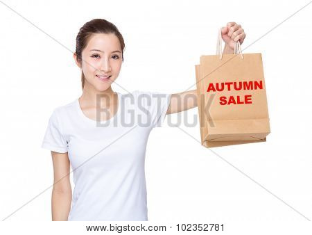 Woman carry with shopping bag and showing phrase of autumn sale