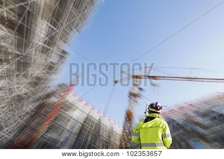 surveyor with measuring-instrument inside large construction site, zoom effect on background