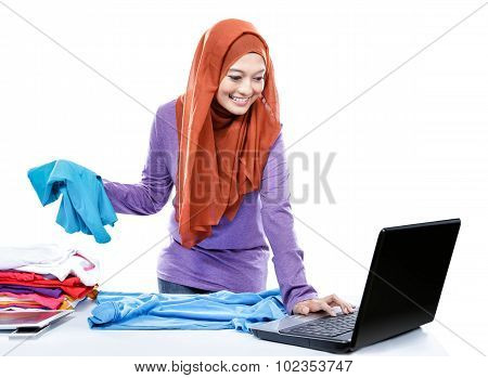 Multitasking Young Woman Wearing Hijab Folding Clean Clothes While Browsing On Laptop