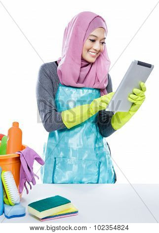 Multitasking Young Housewife Using Tablet While Cleaning A Table