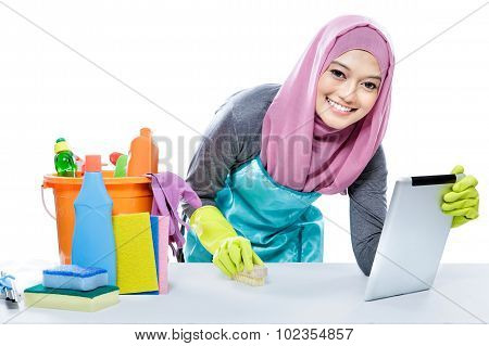 Young Housewife Using Tablet While Rubbing A Table Using Brush
