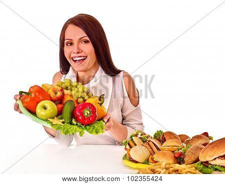 Woman choosing between healthy and unhealthy eating.