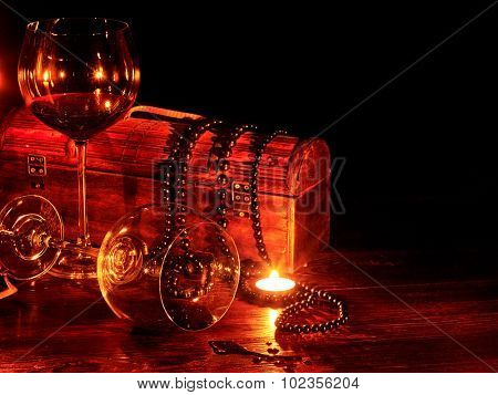 Glass of red spilled wine and burning candle. Antique styling still life.