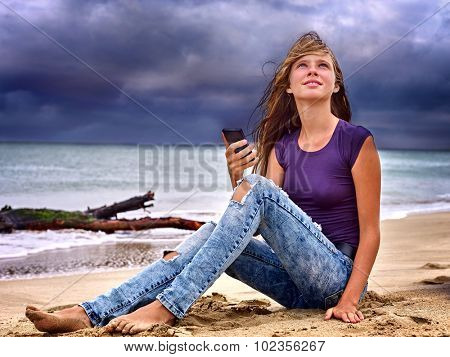 Girl on sand near sea call help by phone. Crash and bad weather.