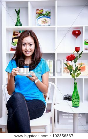 Beautiful Young Woman Sitting At Decorated Living Room While Enjoying A Cup Of Tea