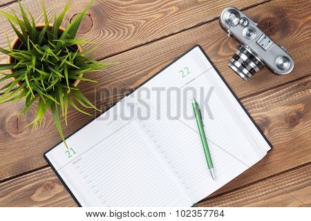 Office desk table with calendar notepad, camera, supplies and flower. Top view