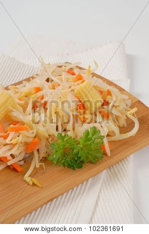 close up of carrot and bean sprouts salad on wooden cutting board and white place mat