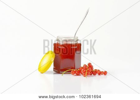 glass jar of fruit jam, with spoon, yellow lid and clusters of fresh red currant, on the white background