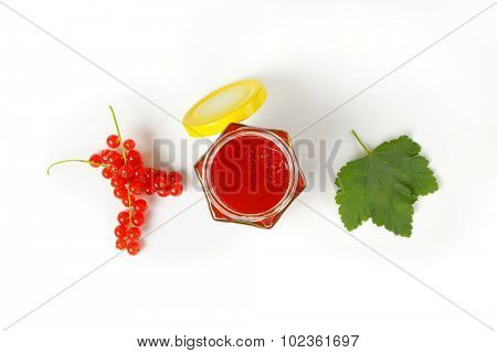 overhead view of glass jar with fruit jam accompanied by clusters of fresh red currant and green leaf
