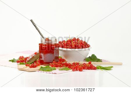 red currant jam filled in glass jar, accompanied by big bowl with clusters of fresh red currant