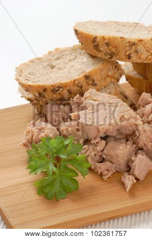 close up of tuna chunks and wholegrain bread on wooden cutting board
