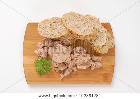 tuna chunks and wholegrain bread on wooden cutting board