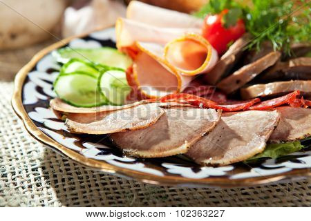 Meat Delicatessen Dish with Cherry Tomatoes and Cucumbers