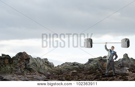 Confident businessman lifting above head stone barbell