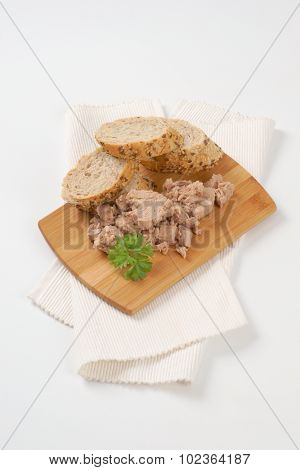 tuna chunks and wholegrain bread on wooden cutting board and white place mat