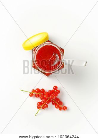 overhead view of opened jar with yellow lid, filled with fruit jam and with immersed teaspoon accompanied by clusters of fresh red currant