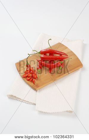 whole and sliced chili peppers on wooden cutting board and white place mat
