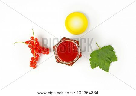 overhead view of glass jar with yellow lid filled with fruit jam, accompanied by clusters of fresh red currant and green leaf