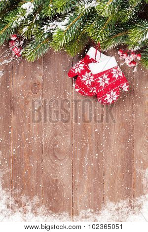 Christmas wooden background with snow fir tree and mittens