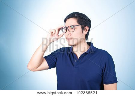 Handsome Asian Man Looking Up While Holding Glasses With Hand, On Blue Background