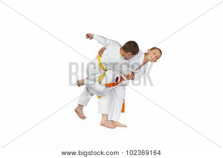 An athlete with an orange belt is doing judo throw