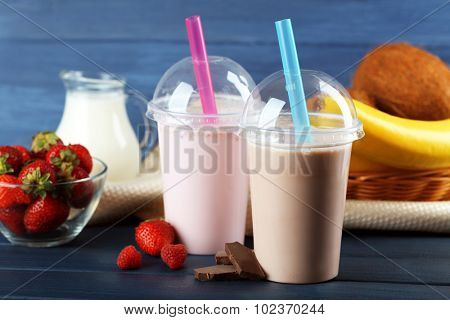 Plastic cups of milkshake on color wooden background