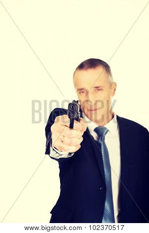 Serious mafia agent aiming by handgun.