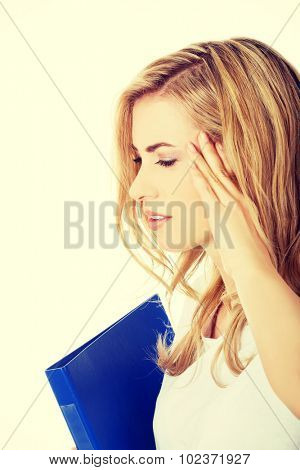 Side view of woman with headache holding a binder.