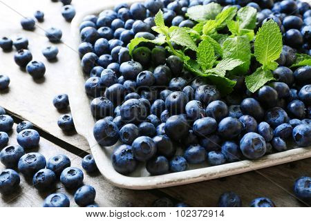 Tasty ripe blueberries with mint on wooden table close up