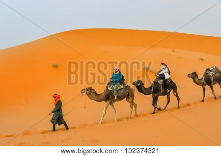 MERZOUGA, MOROCCO, APRIL 13, 2015: Tourists visit Dunes Erg Chebbi near Merzouga during a camel excursion