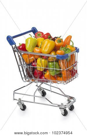 Shopping trolley filled with colorful vine sweet mini peppers on white background