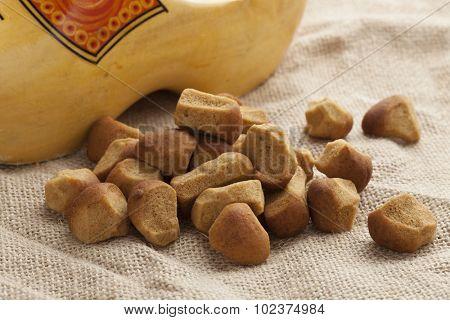 Heap of pepernoten on jute with a dutch wooden shoe