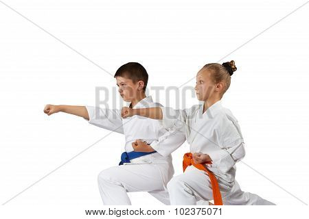 Boy and girl in racks of karate are beating blow hand