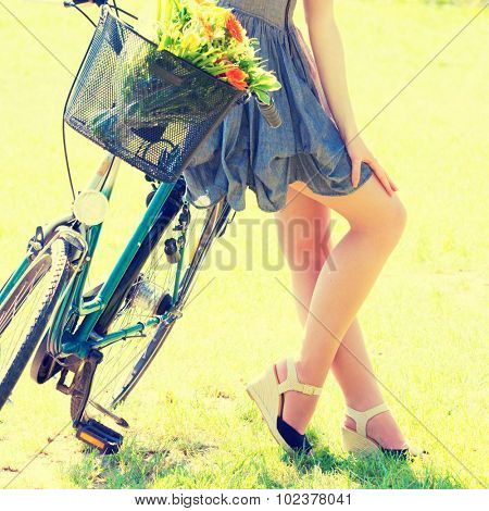 Young woman in short grey dress with long hair rides a bicycle with basket and flowers tour summer city park, look and smile on camera. Toned Pfoto
