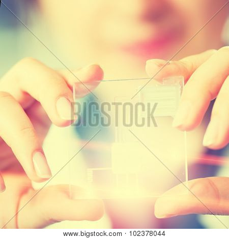 A lab on chip is device integrates several laboratory processes in one device, in woman hand. Toned Pfoto