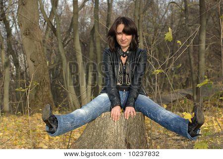 Charming girl sitting on a stump
