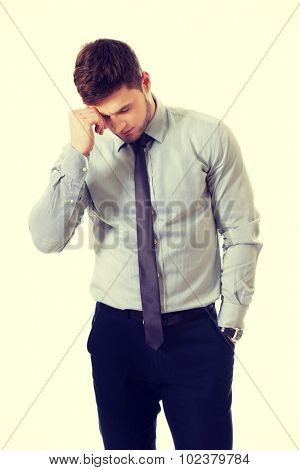Handsome worried businessman touching his forehead.