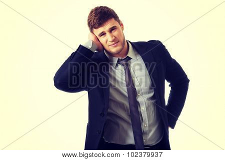 Annoyed businessman covering his painful ear.