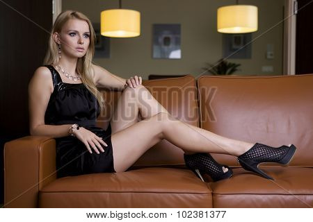 Portrait of a beauty young adult sexy and sensuality attractive pretty blonde woman in black dress sitting on the brown couch
