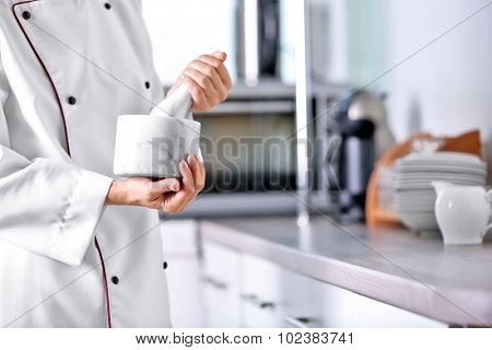 Cook hands with mortar with herbs on bright background