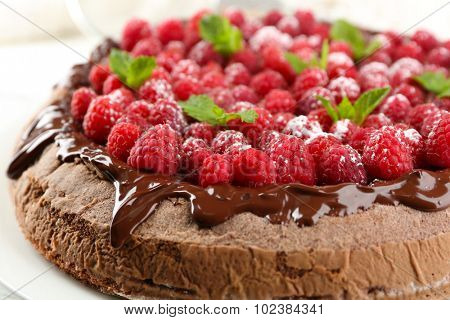 Cake with Chocolate Glaze and raspberries on color wooden background