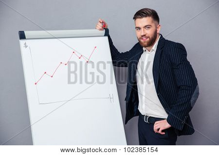 Portrait of a handsome businessman presenting something on board over gray background