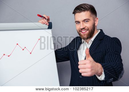 Portrait of a smiling businessman presenting something on board and showing thumb up over gray background