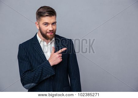 Portrait of a happy businessman pointing finger away over gray background