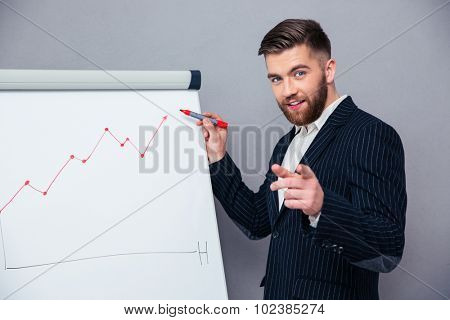Portrait of a happy businessman presenting something on board over gray background